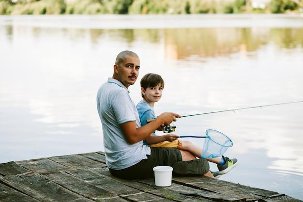 湖で釣る彼の息子と桟橋に座っている男の肖像 無料写真