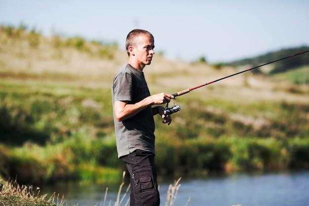 釣り竿を持っている漁師の側面図 無料写真