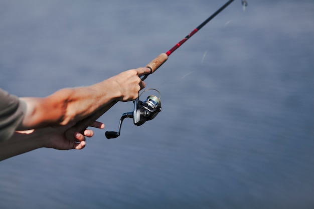 釣りロッドで漁師の手のクローズアップ 無料写真