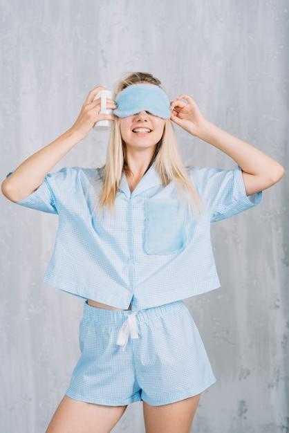 Улыбается молодая женщина, носить синие маски спящего маска против стены Бесплатные Фотографии