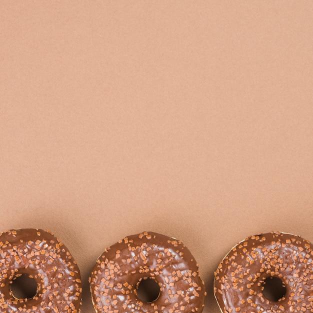 茶色の背景にチョコレートドーナッツ 無料写真
