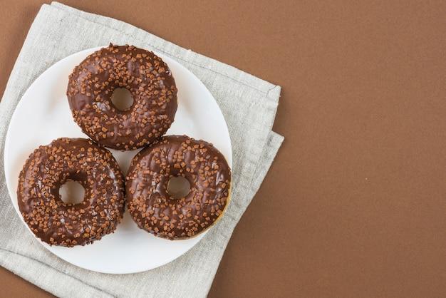 Шоколадные глазурованные пончики на белой тарелке на серой ткани Бесплатные Фотографии