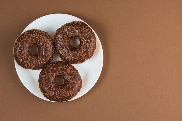 白いプレート上のチョコレートグラスドーナツ 無料写真