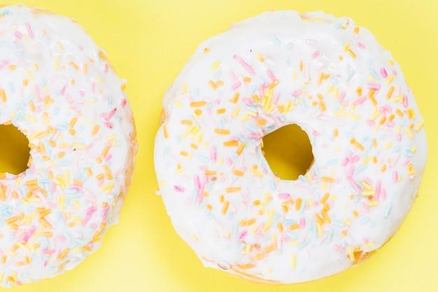 カラフルなスプリンクルと新鮮な砂糖のドーナツ 無料写真