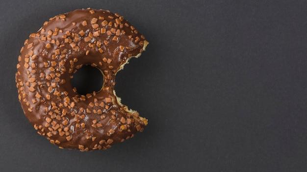 黒の背景に甘いチョコレート噛んだドーナツ 無料写真