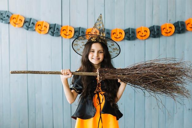 ハロウィーンの衣装の前で十代の女の子はほうきを保持する 無料写真