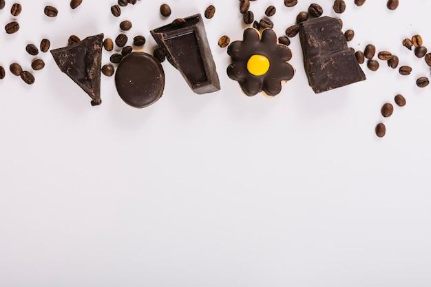 Кусочки шоколада между кофейными зернами Бесплатные Фотографии