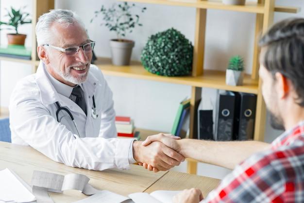 Веселый доктор, пожимая руку пациента Бесплатные Фотографии
