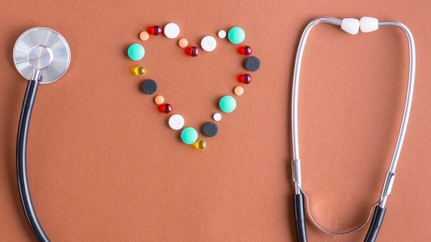 共振器の近くの丸薬と聴診器の耳栓からの心臓 無料写真