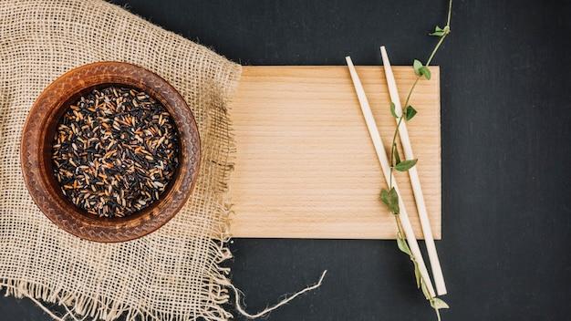 木製のボード上の箸と黒米 無料写真