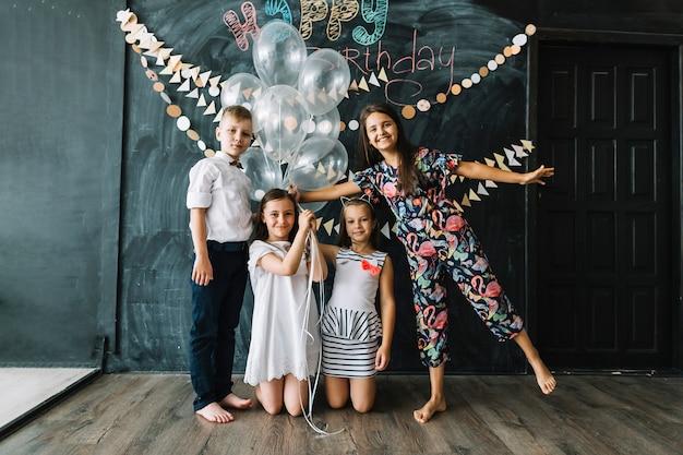 誕生日パーティーで風船でポーズをとる子供たち 無料写真