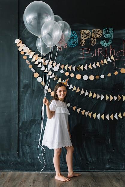 誕生日の装飾の近くに風船を持つ素足の少女 無料写真