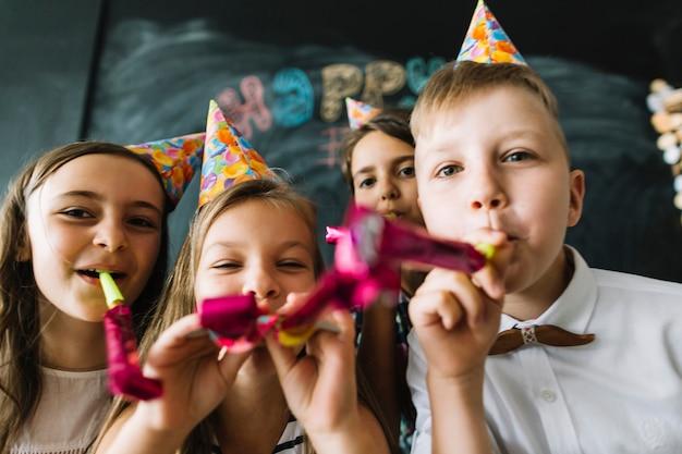 一緒にカメラでパーティーの角を吹く子供たち 無料写真