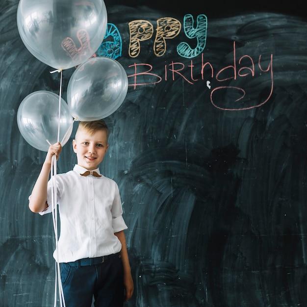 幸せな誕生日の書き込みの近くに風船を持つ少年 無料写真
