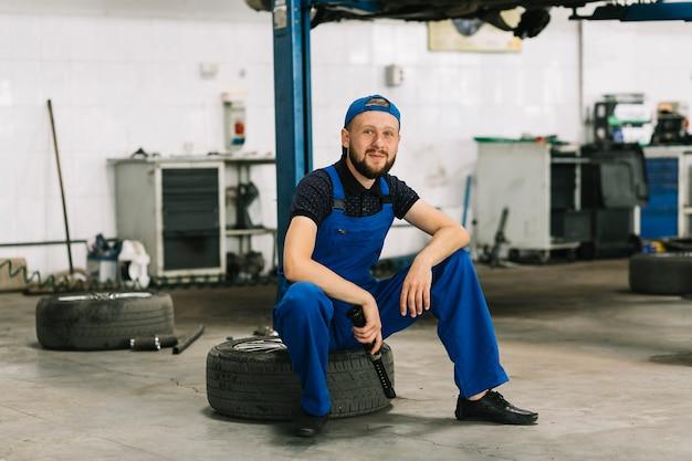 ガレージでタイヤに座って修理士 無料写真