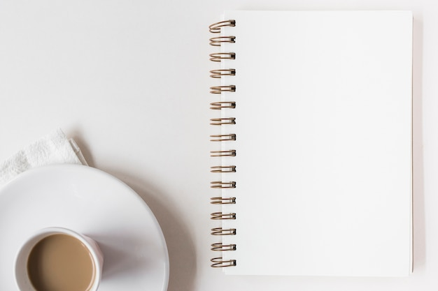 白い背景にコーヒーカップと空のスパイラルメモ帳 無料写真