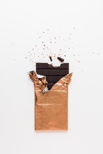 白い背景に一口の欠けた黄金の箔で包まれたダークチョコレートバー 無料写真