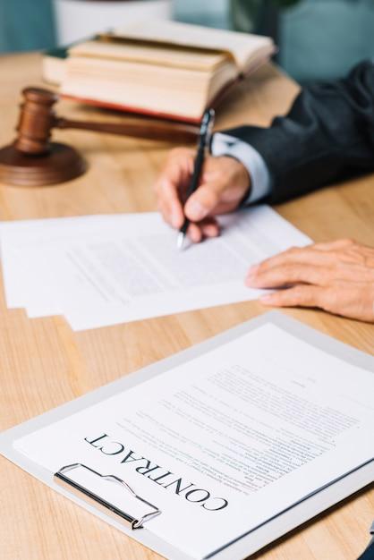 裁判官の近くの契約書類のクローズアップは机上の文書を調べる 無料写真