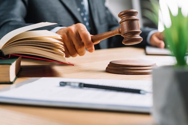男性の裁判官は、机の上で槌を打つことによって判決を下す 無料写真
