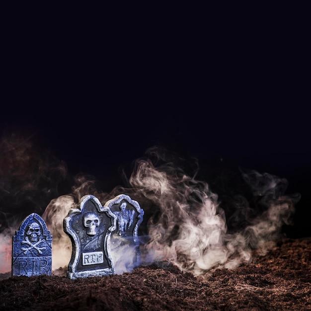 地面の霧の間の照らされた墓石 無料写真