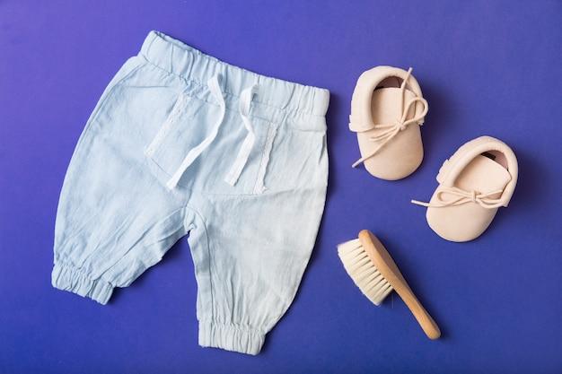ペアのベビーシューズ;青い背景にブラシと赤ちゃんのパンツ 無料写真