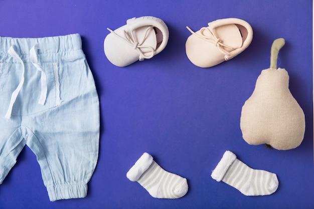 ピンクのベビーシューズ;明るい青色の背景に詰めた梨と靴下と赤ちゃんのパンツ 無料写真