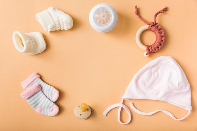 ベビーの靴下;羊毛の靴のペア;おしゃぶり;キャップ;牛乳びん;オレンジの背景におもちゃ 無料写真