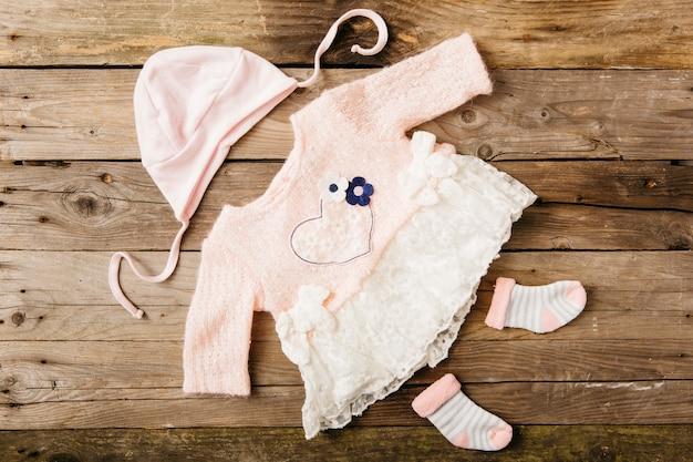 帽子と木製のテーブルに靴下のペアとピンクの赤ちゃんのドレス 無料写真