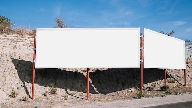 道路の近くに白い空の広告掲示板 無料写真