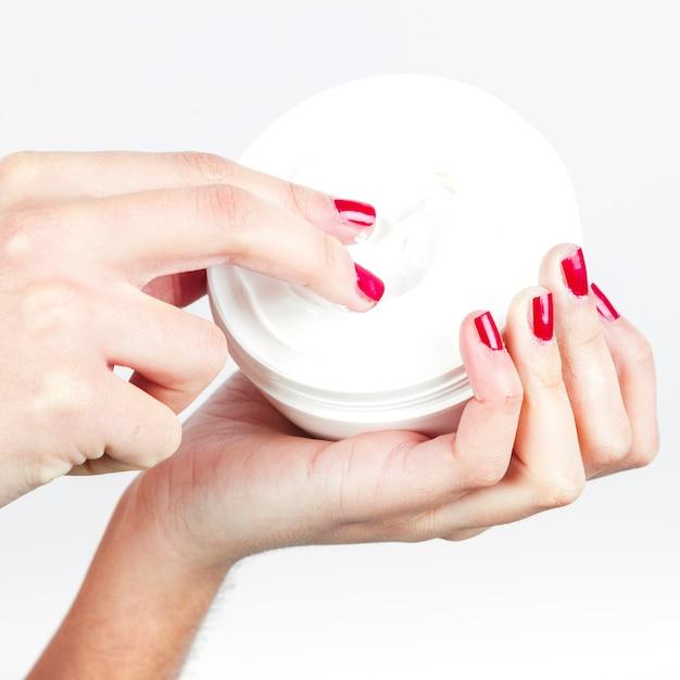 モイスチャライジングクリームを塗っている女性の指のクローズアップ 無料写真