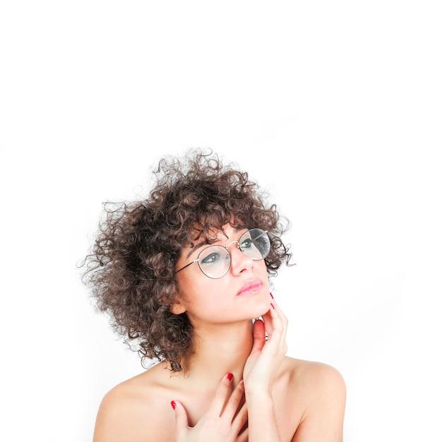 彼女の頬に触れる眼鏡を着ている魅力的な女性は、白い背景の上に 無料写真