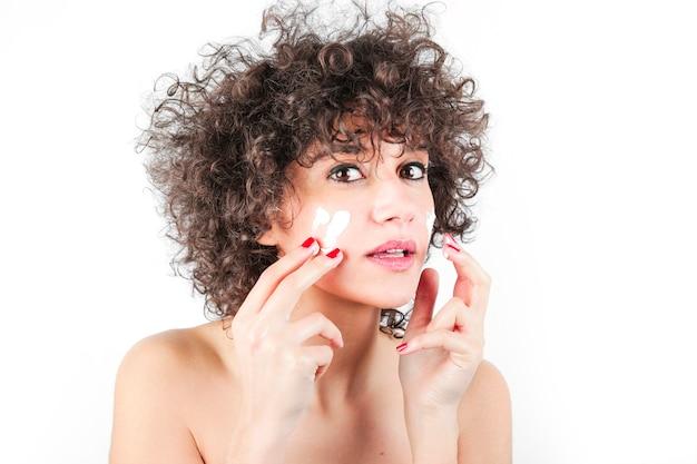 Красивая модель, применяя косметический крем, лечение на ее лице на белом фоне Бесплатные Фотографии