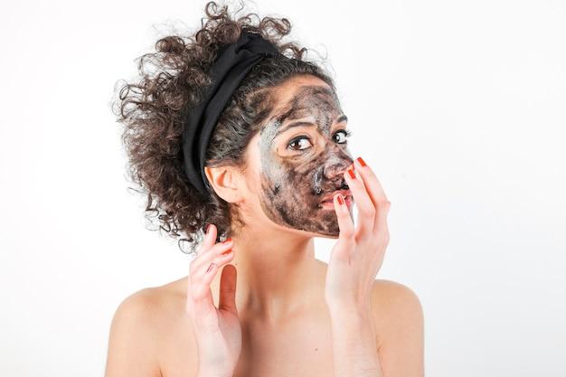 白い背景の上に彼女の顔にフェイシャルマスクを適用している美しい若い女性 無料写真