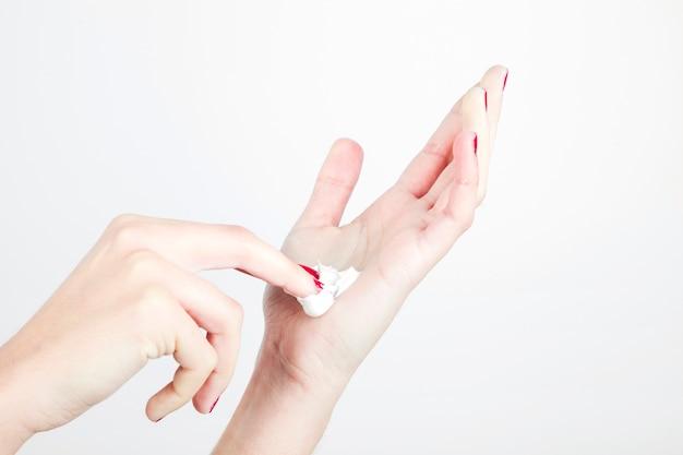 クローズアップの女性の手はモイスチャライザーは、白い背景に 無料写真