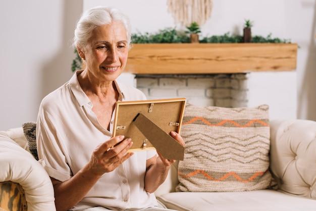 写真のフレームを見てソファーに座っている幸せな高齢の女性 無料写真