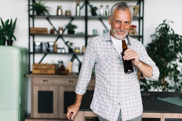 Улыбаясь старший человек, пить пиво из бутылки дома Бесплатные Фотографии