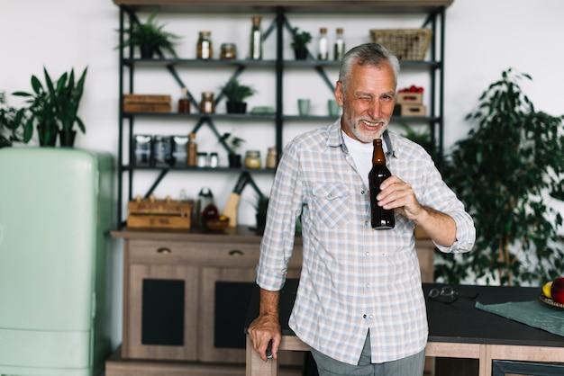 Улыбающийся пожилой мужчина подмигивает ему, держа в руке пивной бутылку Бесплатные Фотографии