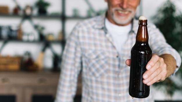 Крупный план старшего человека, предлагающего бутылку пива Бесплатные Фотографии