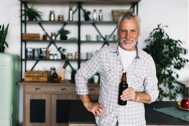 Портрет улыбающегося старшего человека, стоящего в кухне, проведение бутылку пива Бесплатные Фотографии