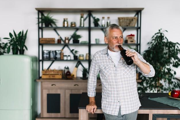 Пожилой мужчина, стоящий перед кухонным прилавком, пить пиво Бесплатные Фотографии