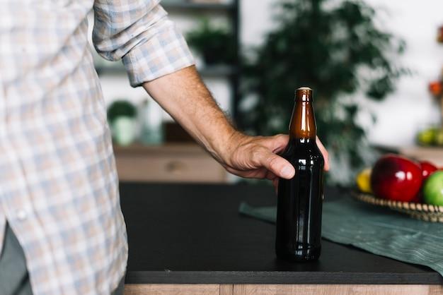 Крупный план человек, держащий бутылку пива на кухне счетчик Бесплатные Фотографии
