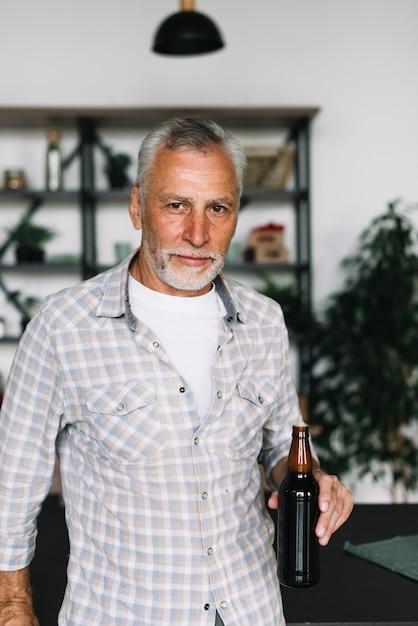 Портрет пожилой человек с бутылкой пива в руке Бесплатные Фотографии