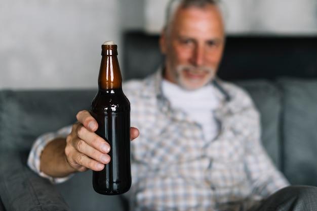 Крупный план старший мужчина показывает бутылку пива с пеной Бесплатные Фотографии