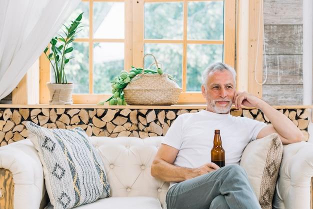 Улыбаясь старший человек, сидя на диване, проведение бутылку пива Бесплатные Фотографии