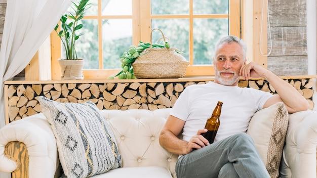 Пенсионер пожилой человек, проведение пивной бутылки, сидя на диване Бесплатные Фотографии
