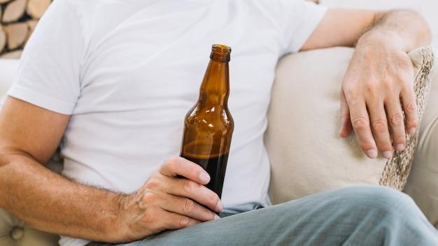 Крупным планом человек, держащий бутылку пива Бесплатные Фотографии