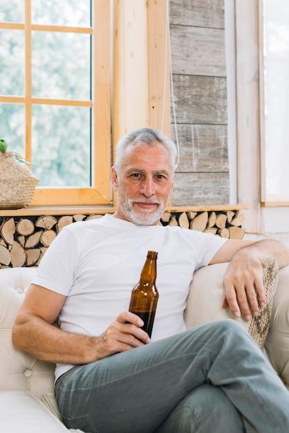 Портрет старшего человека, сидящего на диване, глядя на камеру, проведение бутылку пива Бесплатные Фотографии