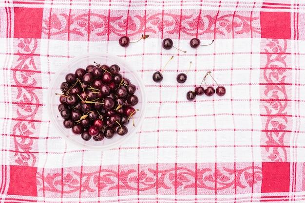 ナプキンに赤いチェリーのボウル 無料写真