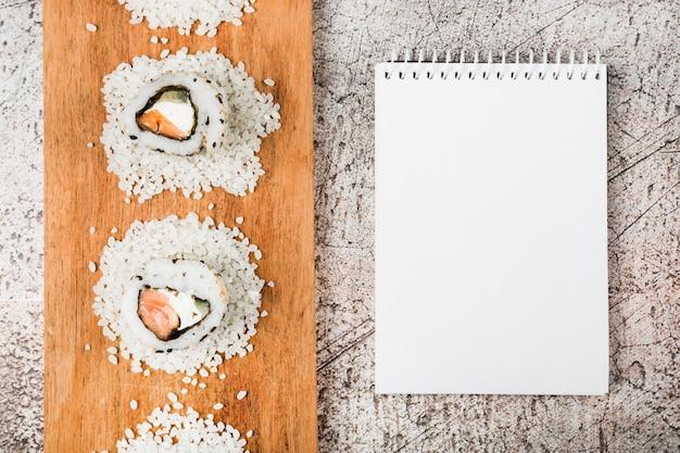 素朴な背景に空の螺旋メモ帳と木製トレイに寿司ロールのトップビュー 無料写真