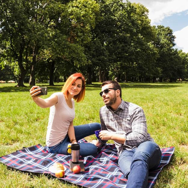 屋外のピクニックで携帯電話でセルフを取る若いカップル 無料写真